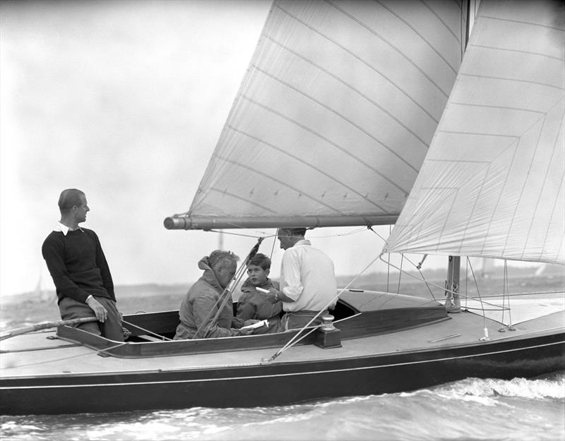 Charles, Prince of Wales with his father the Duke of Edinburgh and crew members Uffa Fox, the Duke's Yachting adviser and Lieutenant-Commander Alistair Easton, Sailing Master of the yacht