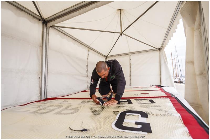 John McAfee putting numbers on a sail at the Musto Skiff Worlds - photo © Bernardi Bibiloni
