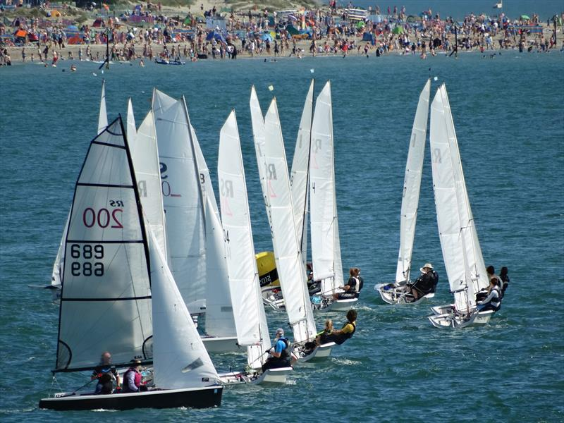 RS200s at the windward mark on Friday, with the crowds on West Wittering beach in the background at Chichester Harbour Race Week - photo © Liz Sagues