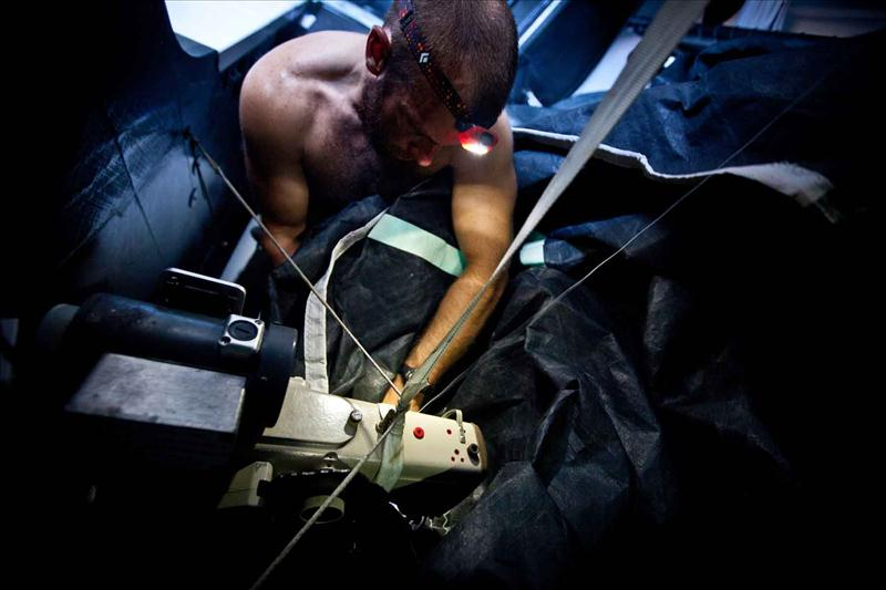 Ryan Godfrey at work repairing a ripped sail on PUMA Ocean Racing in leg 4 photo copyright Amory Ross / PUMA Ocean Racing / Volvo Ocean Race taken at  and featuring the Volvo 70 class