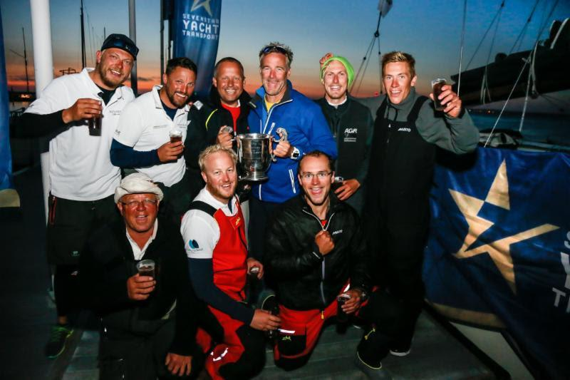 Giles Redpath (Centre holding winners trophy for IRC One) and crew celebrate dockside - photo © Paul Wyeth / RORC
