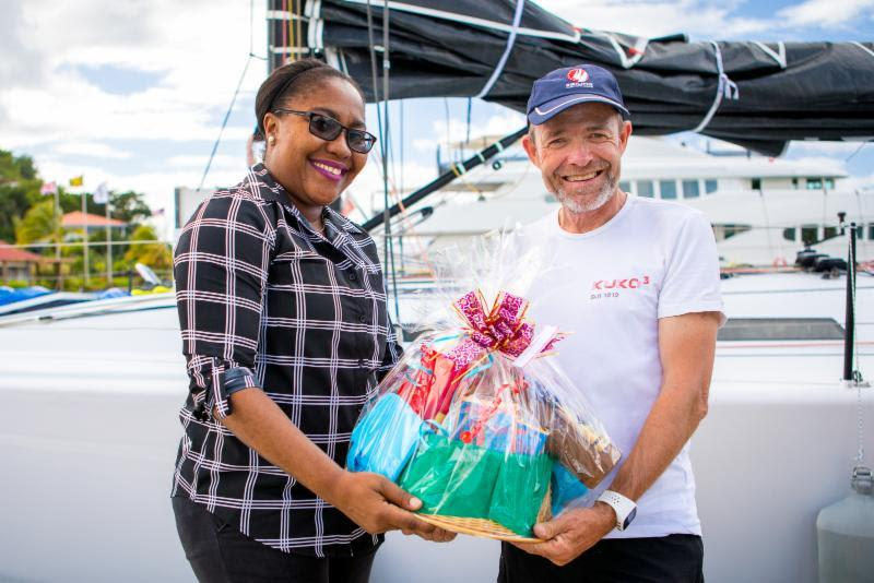 A welcome basket of Grenadian specialities is handed over to Kuka3's owner on arrival by Chinel Sandy from the Grenada Tourism Authority - 2018 RORC Transatlantic Race photo copyright RORC / Arthur Daniel taken at Royal Ocean Racing Club and featuring the IRC class