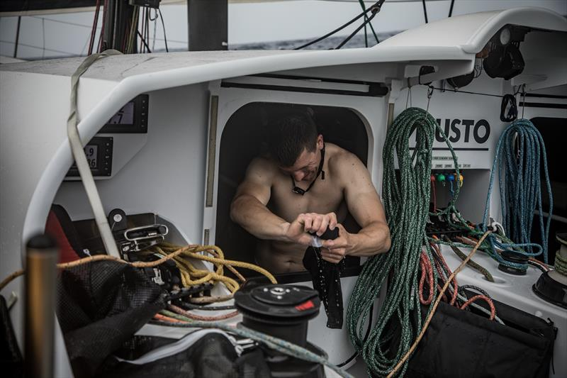 Onboard team Brunel Carlo Huisman tries to dry out some of his kit - photo © Martin Keruzore / Volvo Ocean Race