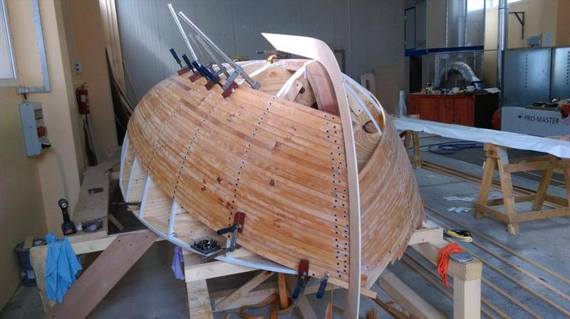 Croatian Gajeta build - As the planking advances, a template of the CNC outer keel is offered up to ensure the shape is correct - photo © West System International